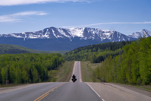 Motorcyclist driving on Highway 40 towards Grande Cache and the Rocky Mountains, northern Alberta, Canada.