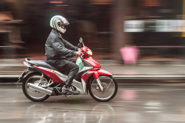 motorcyclist in bangkok, thailand - motorbike, umbrella stock pictures, royalty-free photos & images
