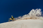 Motorcyclist riding his bike across sand dunes.