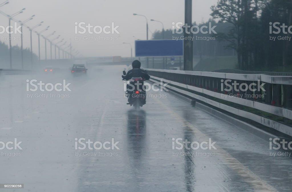 Motorradfahrer fährt Motorrad mit Regenwetter – Foto