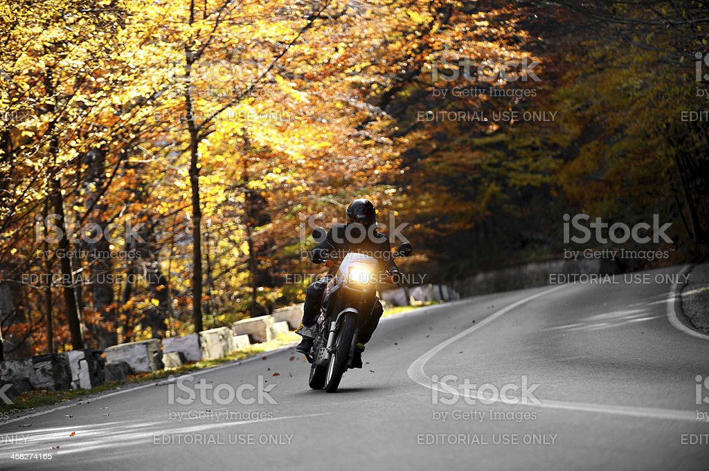 Motorcyclist On A Winding Road In Autumn stock photo