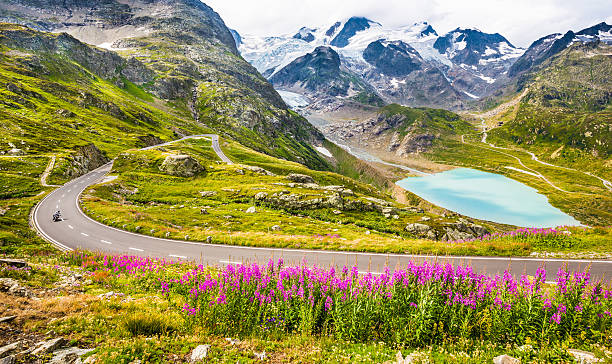 Motorcyclist on mountain pass road in the Alps stock photo