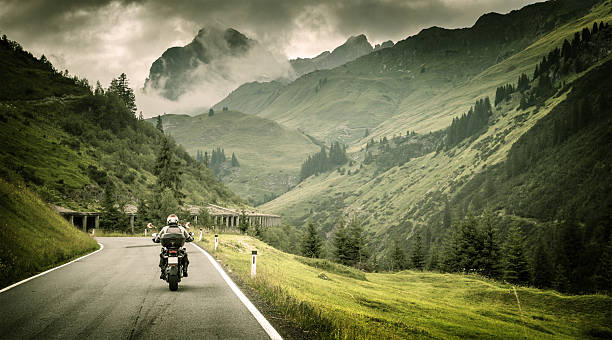 motorcyclist on mountainous highway - motorcycle stock photos and pictures