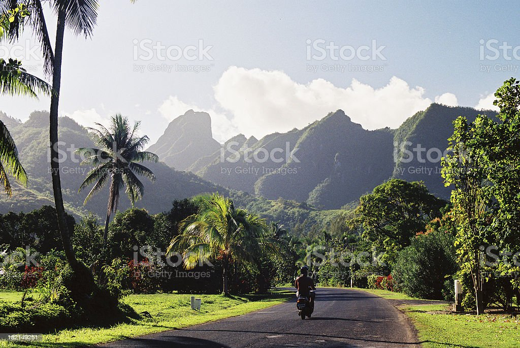 Motorcyclist on Polynesian road stock photo