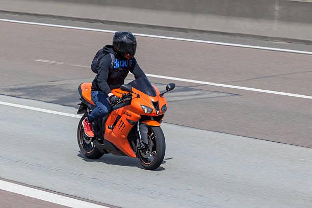 Motorcyclist on the Kawasaki Ninja Frankfurt, Germany - July 12, 2016: Motorcyclist on the orange Kawasaki Ninja ZX-6R  motorcycle   kawasaki heavy industries stock pictures, royalty-free photos & images
