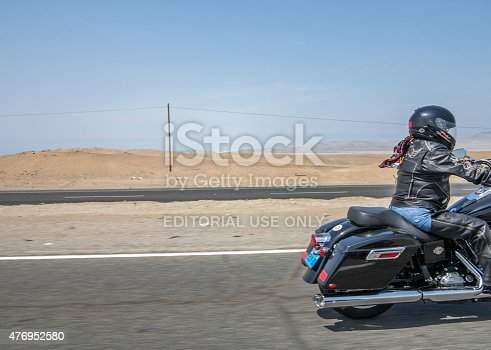 Huaral, Peru - January 22, 2015: Harley Davidson female Motorcyclist on the pan-american highway in Peru. View of the rear half of the bike and rider leaving the composition.