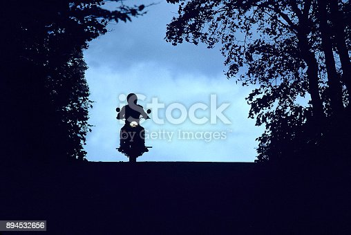 Silhouette of motorcyclist on vintage motorcycle.