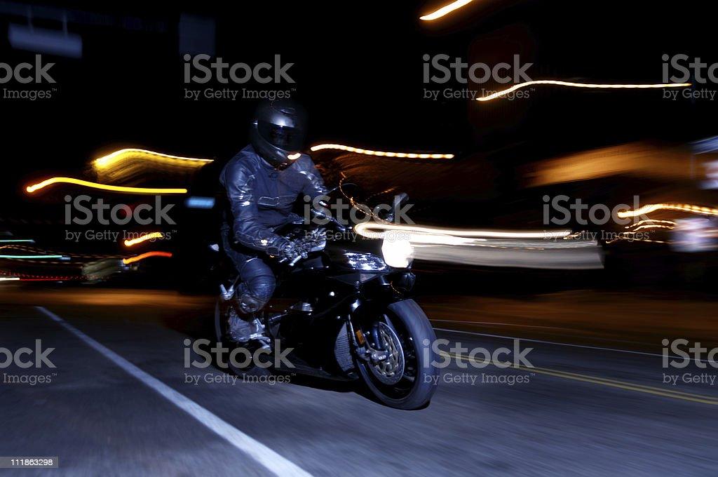 Motorcyclist Racing down City Street at Night royalty-free stock photo
