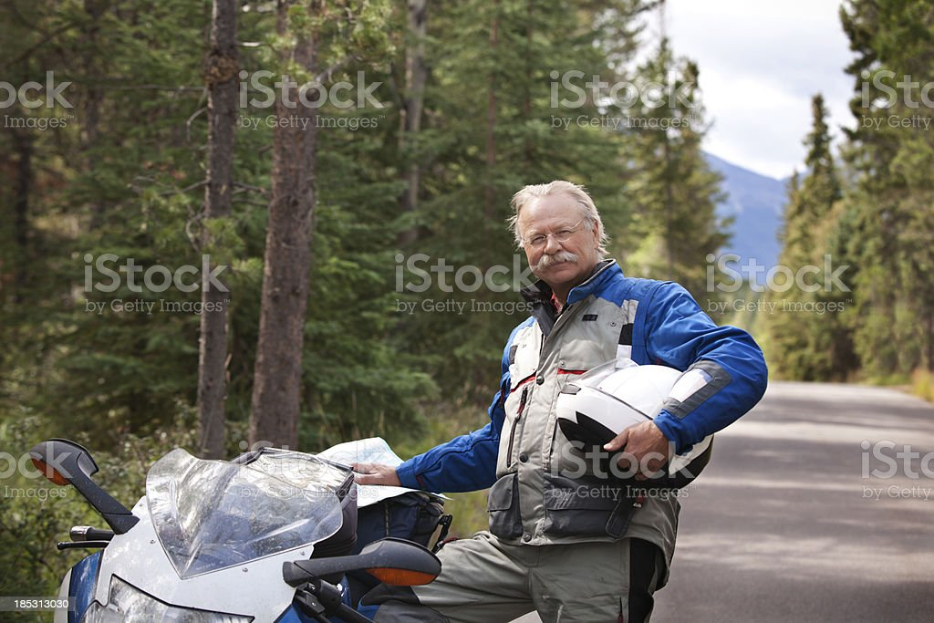 Motorcyclist reading map with motorcycle on road. stock photo