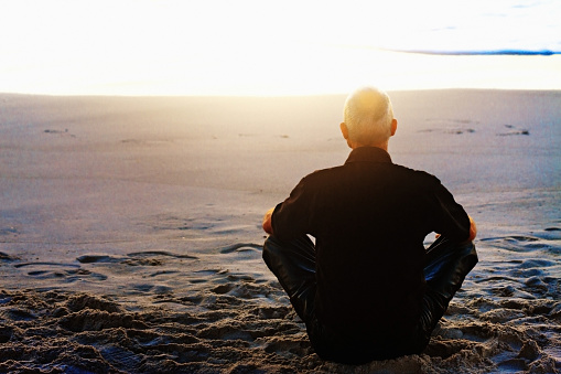 Rear view of a man in black, in fact motorcyclist's leathers, seated cross-legged on a beach, meditating on the sunset or sunrise.