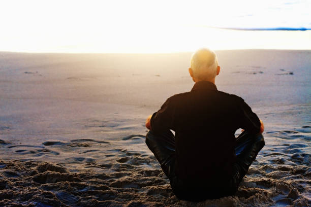 Motorcyclist sitting cross-legged, meditating, on beach at sunset Rear view of a man in black, in fact motorcyclist's leathers, seated cross-legged on a beach, meditating on the sunset or sunrise. yogi stock pictures, royalty-free photos & images
