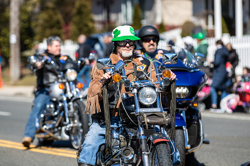 Motorcyclist wearing a green hat riding in the first Annual St. Patrick's Day Parade