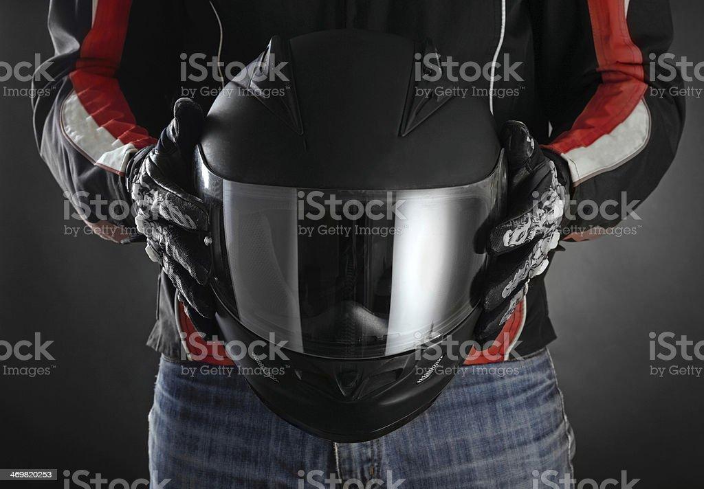 Motorcyclist with helmet in his hands. Dark background stock photo