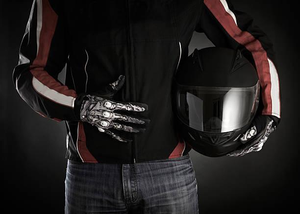 Motociclista con casco en sus manos.  Fondo oscuro - foto de stock
