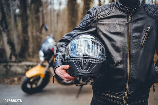 Motorcyclist holding helmet equipment
