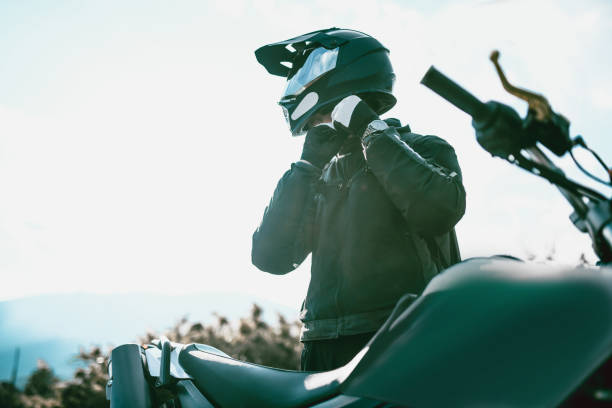 motorcyclist with specialized equipment getting ready to ride - crash helmet stock photos and pictures