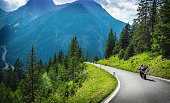 Motorcyclists in mountainous touring, extreme adventure, European journey, extreme road along Alps, active holiday concept