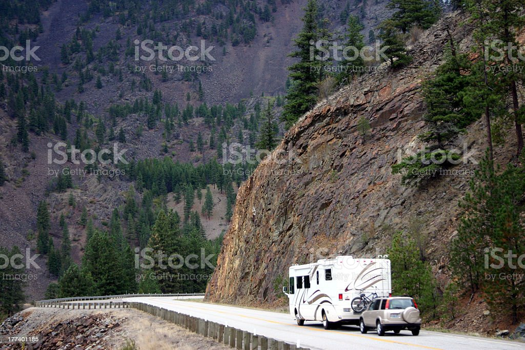 RV motorhome followed by SUV on a mountain highway stock photo