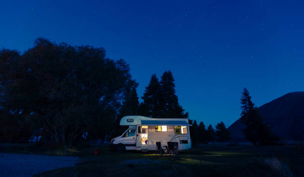 Motorhome on campsite at night. Can use for summer or holiday concept background. Motorhome on campsite at night. Can use for summer or holiday concept background. motor home stock pictures, royalty-free photos & images