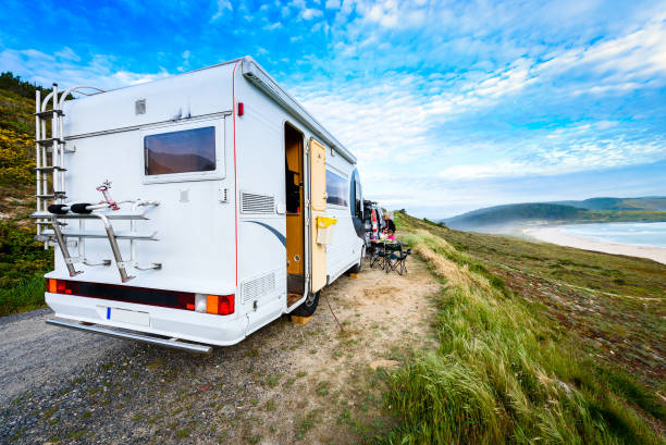 Motorhome RV and campervan are parked on a beach. Motorhome RV and campervan are parked on a beach. Family on vacation is sitting outsides on camping chairs and table having dinner, with amazing view of the beach and ocean. Atlantic beach - Spain. motor home stock pictures, royalty-free photos & images