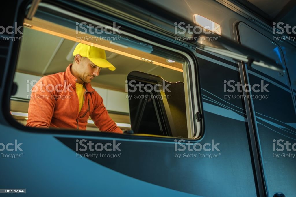 Motorhome RV Owner Caucasian RV Owner In His 30s Inside His Motorhome Cleaning Kitchen Section Adult Stock Photo