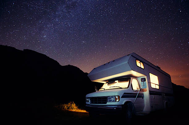 Motorhome Under the Stars A small illuminated motorhome at night under the stars. motor home stock pictures, royalty-free photos & images