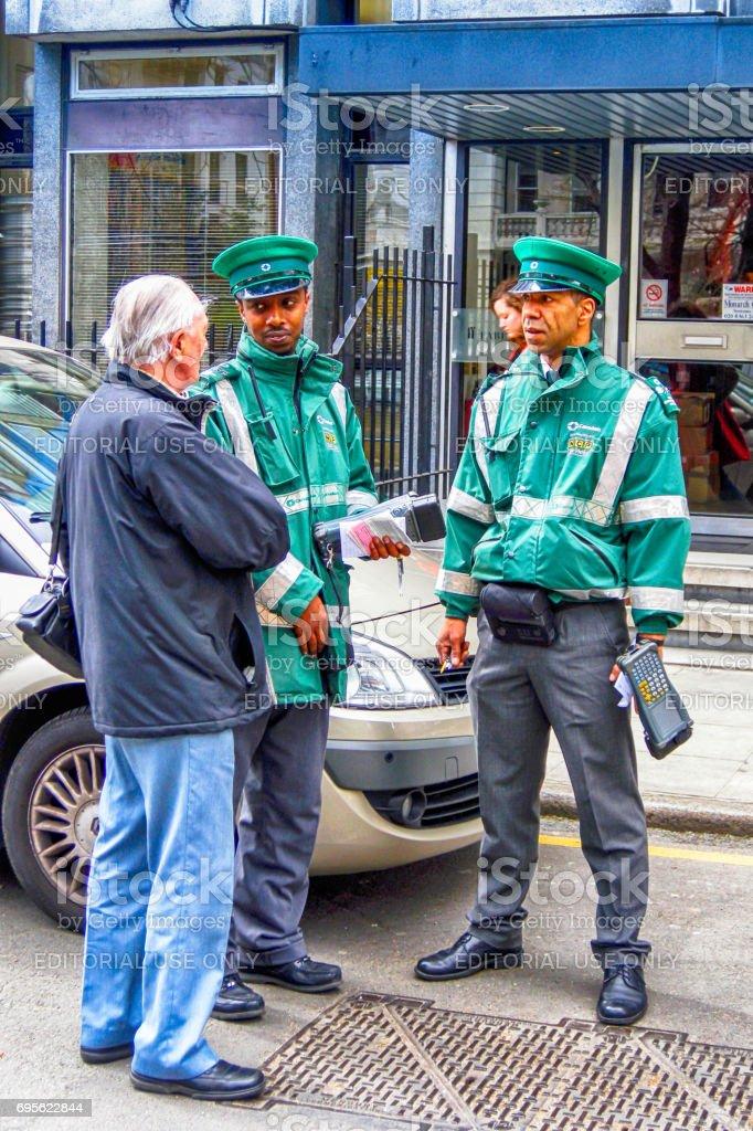 Motorista, discutindo com dois oficiais de controle de estacionamento em central London, UK - foto de acervo