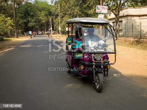Bolpur, West Bengal ,India - November 30, 2018: An electric-powered rickshaw parked in a market in Bolpur in India. These motorized rickshaws are providing an alternative to human-powered cycle rickshaws for transportation in many parts of India.