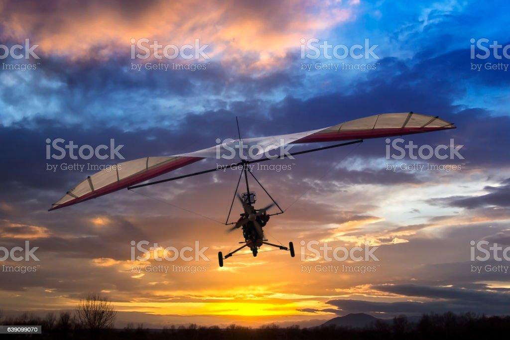 Motorized hang glider flying in the sunset - foto de acervo