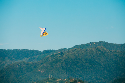 Motorized Hang Glider Flying Over Mountain Hills In Blue Clear Sunny Sky
