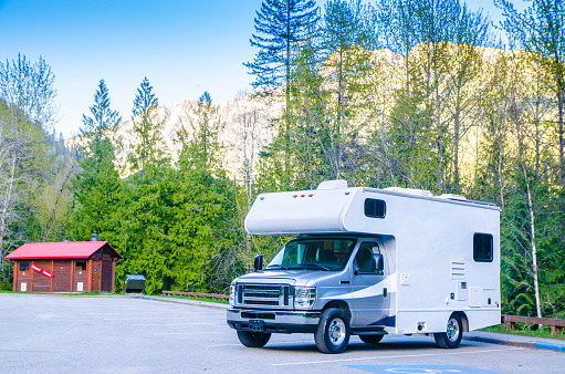Motorized home parked in rest area in British Columbia with Rocky mountains behind