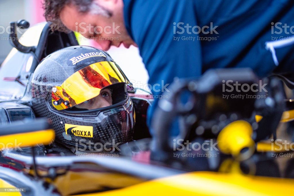 Member of a motorsport team helping the driver of a formula race car...