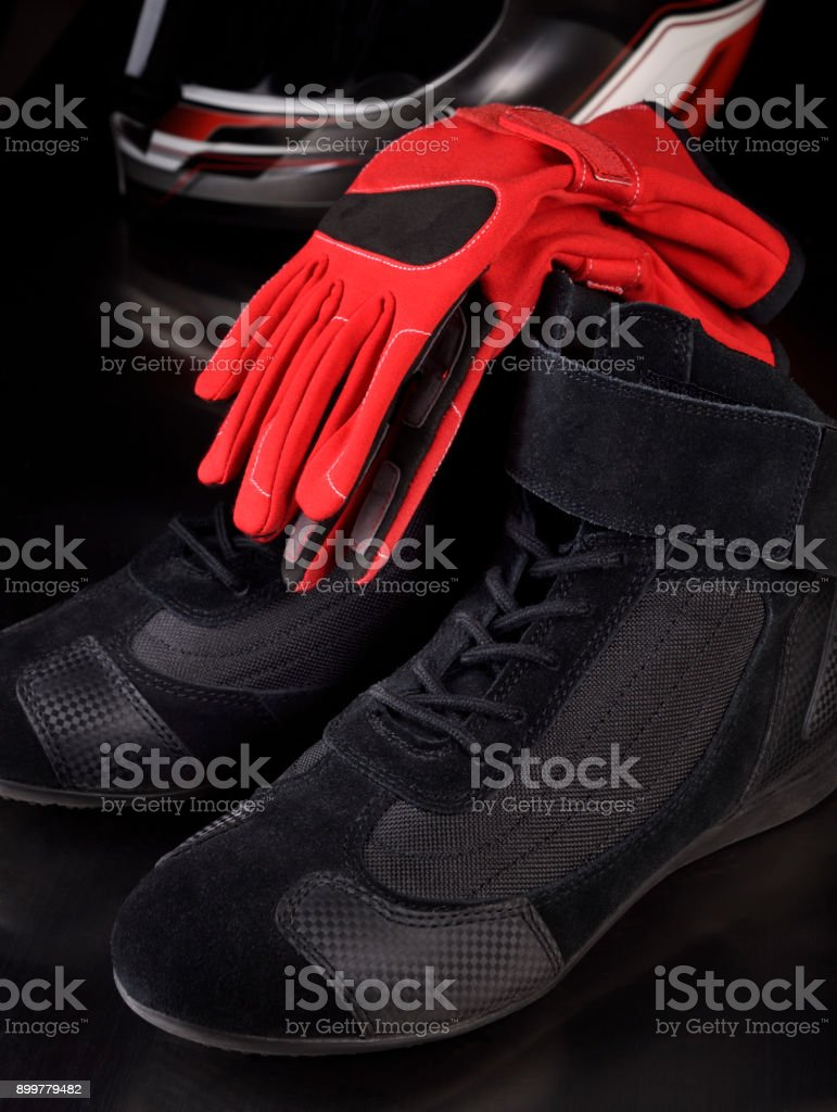 Black racing shoes, red gloves and helmet for motorsport racing