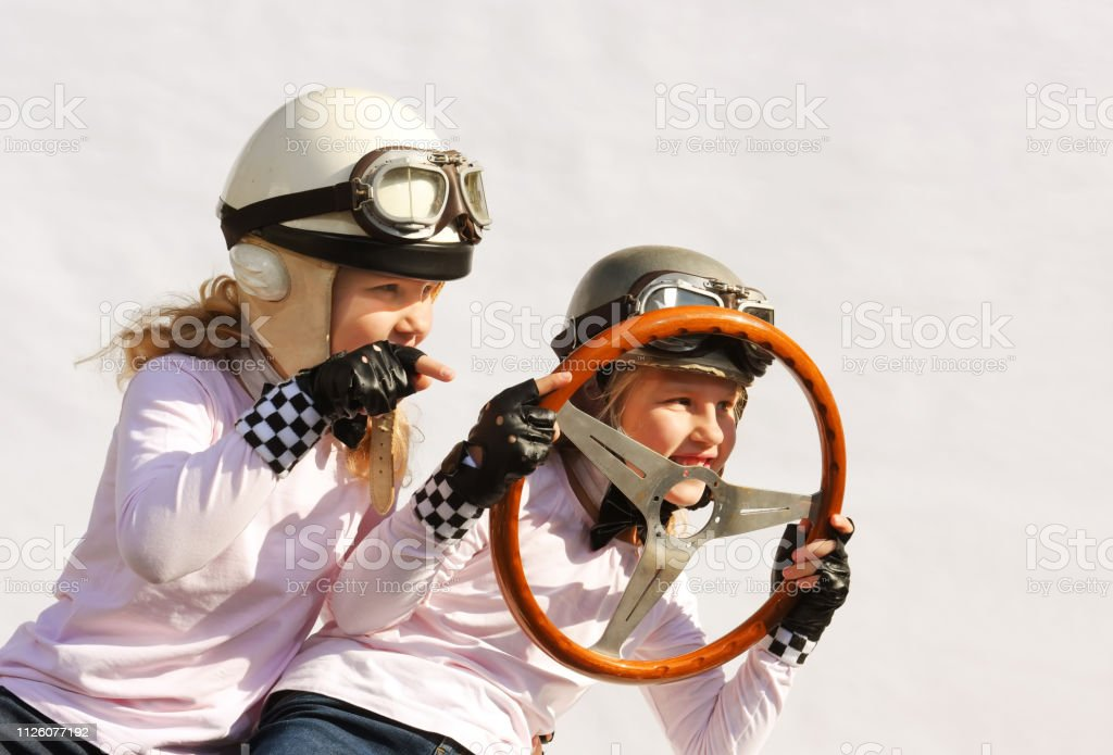 Twin sisters play race car driver sitting in their imaginative sports...