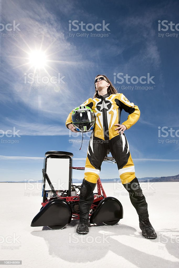 Low angle hero shot of a female racer dressed in protective leather...