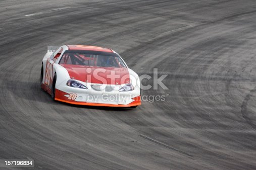 A late model stock car racing on an oval track. Room for copy.