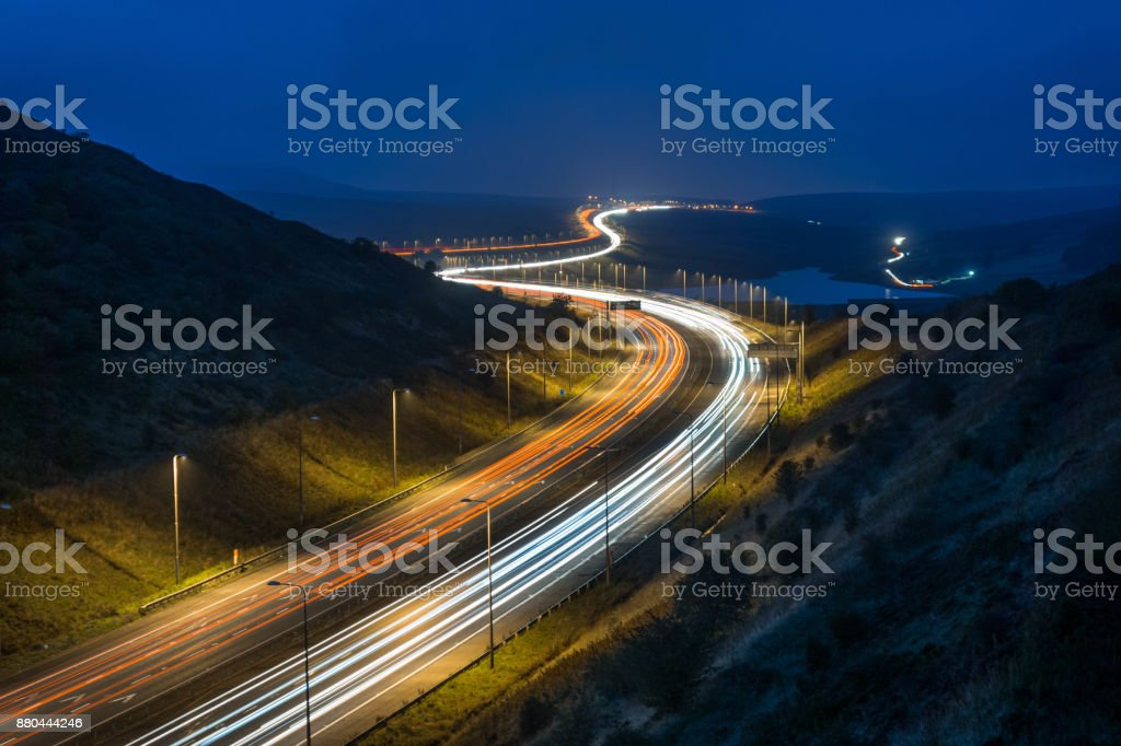 A motorway in England sweeps through the countryside at night stock photo