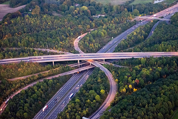 M25 Motorway interchange Sinuous curves of M25 motorway interchange at dusk, the street lights are on and cars are travelling along the 4 layer elevated jmajor road junction. overpass road stock pictures, royalty-free photos & images