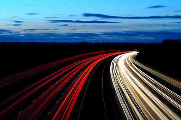 autobahn bei sonnenuntergang - zweispurige strecke stock-fotos und bilder