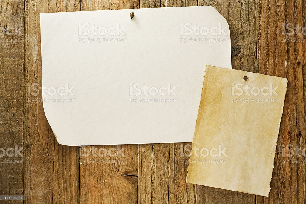 mottled beige paper nailed to distressed wooden wall stock photo