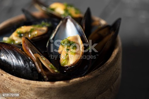 closeup of a boxwood bowl with moules mariniere, a french recipe of mussels, on a rustic wooden table