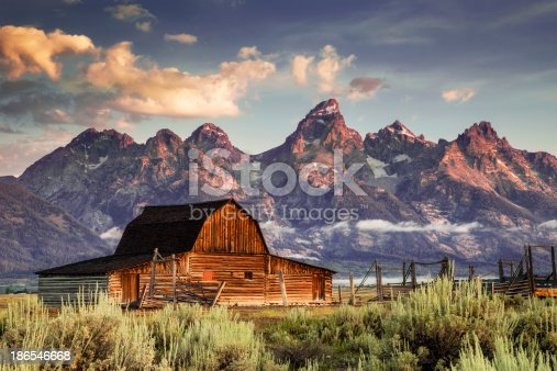 Early morning magenta light illuminates clouds and the Moulton Barn on Mormon Row at the foot of the Grand Tetons near Jackson, Wyoming, USA.