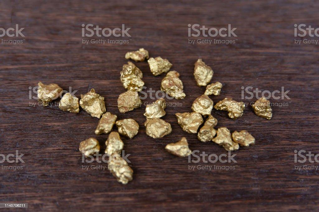 mound of gold nugget on dark wood background
