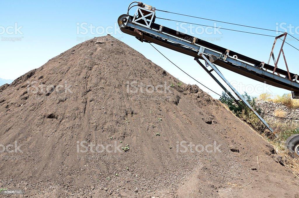 Mound of topsoil under conveyor belt stock photo