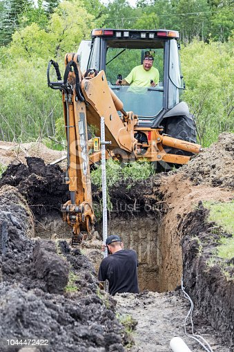 Erskine, USA - June 25, 2018:  A new residential mound septic system is being installed. A worker is operating a backhoe to dig the hole for a septic tank while another worker is standing in the hole taking measurements.