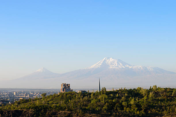 Mount Ararat viewed from Yerevan, Armenia Early morning view of Mount Ararat viewed from Yerevan, Armenia. The spire in the foreground is part of the Tsitsernakaberd (Armenian Genocide Memorial complex). armenian genocide stock pictures, royalty-free photos & images