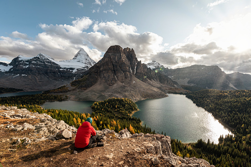 Mount Assiniboine with rocky mountains and lake in autumn forest at provincial park, BC, Canada. Traveler relaxing on the Niblet