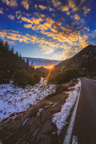 Mount Baldy Sunset Sunset at snow-covered Mount Baldy in winter with a road winding through the tall peaks and colorful clouds in the sky, San Gabriel Mountains, San Bernardino County, California mount baldy stock pictures, royalty-free photos & images