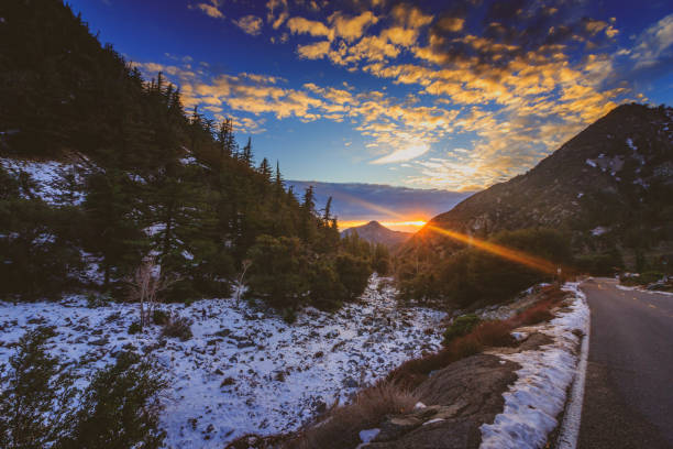 Mount Baldy Sunset Sunset at snow-covered Mount Baldy in winter with a road winding through the tall peaks and colorful clouds in the sky, San Gabriel Mountains, San Bernardino County, California san bernardino california stock pictures, royalty-free photos & images