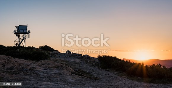 Panoramic image of the Fire Tower on Mount Coree (Canberra, Australia) backlight by a beautiful soft sunset.